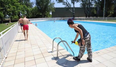 Una empleada desinfecta les escales el primer dia d'obertura de les piscines de Sucs.
