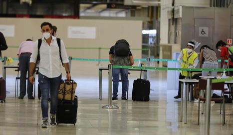Diverses persones a l'arribar a la terminal 4 de l'aeroport de Madrid-Barajas.
