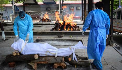 Dos operaris es disposen a cremar el cos d'una víctima del coronavirus en un crematori a Nova Delhi, Índia.