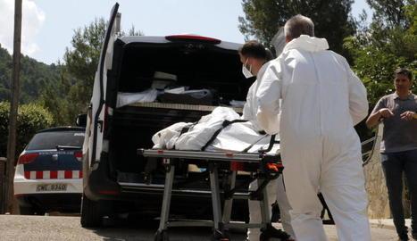 Els serveis funeraris s'emporten el cos de la dona assassinada.