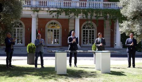 El president, part del seu Executiu i agents socials van escenificar l'acord en una foto conjunta als jardins de La Moncloa.