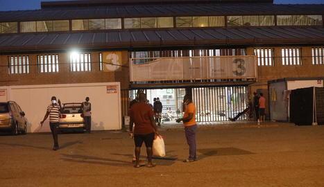Diverses persones conversen ahir a la nit davant l'entrada del pavelló 3 de la Fira on pernocten.