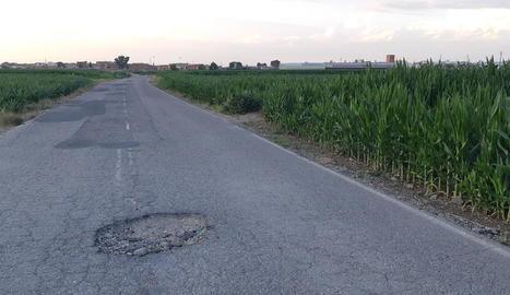 El clot que hi havia al camí que connecta Fondarella i Miralcamp i un operari reparant-lo.