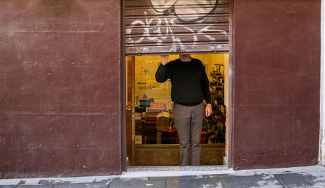 Un treballador autònom tanca el negoci al final de la jornada.