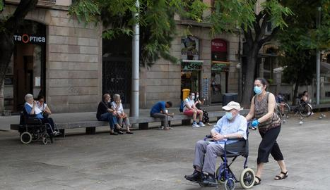 Una dona passeja un home pels carrers de Barcelona equipats amb mascaretes.