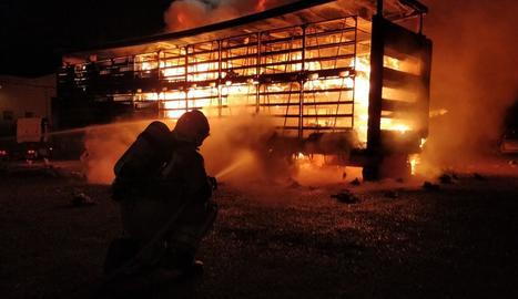 Un bomber sufocant ahir l'incendi que va calcinar part del camió.