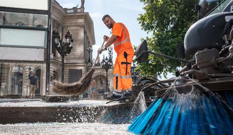 Un operari neteja la zona en la qual es va produir el 'botellón'.