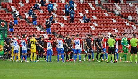Jugadors de l'Sporting fan el passadís als de l'Osca.