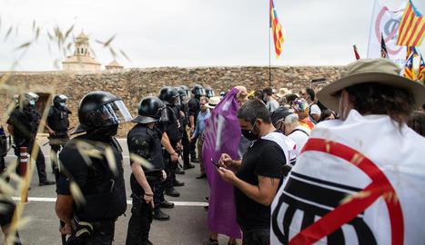 A l'esquerra, els reis a Poblet amb Illa i Cunillera. A la dreta, els Mossos van impedir que els manifestants s'atansessin al monestir.