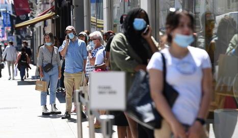 Diverses persones fan cua a Londres per entrar a una botiga.