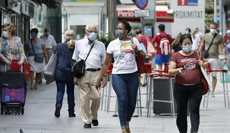 Diverses persones passegen amb mascareta per l'Hospitalet.
