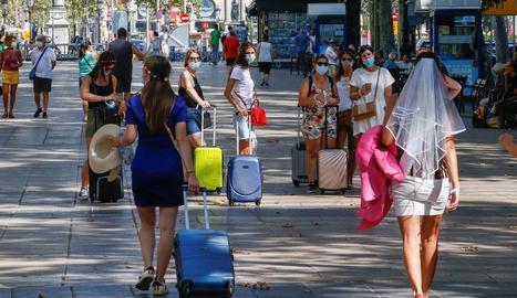 Diverses turistes caminen per la Rambla de Barcelona.