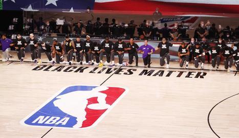 Els jugadors dels Lakers i els Clippers s'agenollen durant l'himne nacional dels EUA.