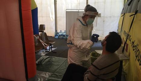 Una professional sanitària efectua una prova PCR a un pacient a la carpa davant el CAP de Prat de la Riba.
