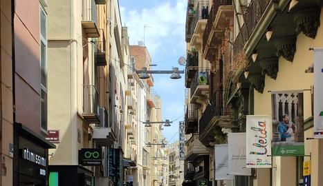 Nombroses persones passejant per l'Eix Comercial de Lleida ahir al migdia.