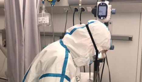Un sanitari atén un pacient en una de les plantes Covid de l'Arnau.