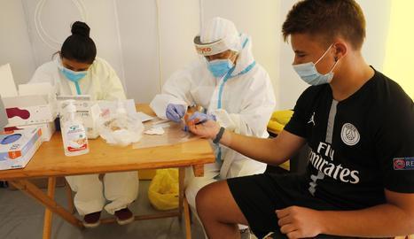 Sanitaris fan un test serològic a un jove a Alcarràs.