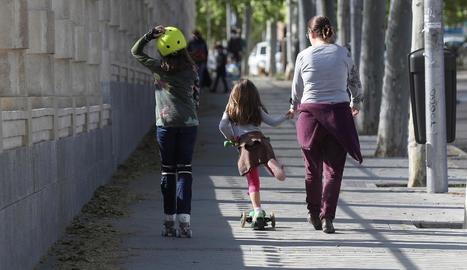 Una mare, a finals del curs passat, al sortir de classe amb dos nenes.