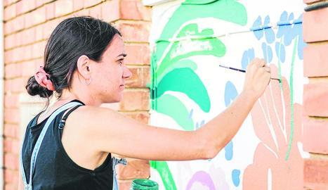 L'artista Lara Costafreda pintant l'exterior de l'escola.