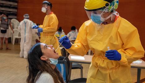 Una jove és atesa per un professional sanitari al Centre Cívic del barri de Balàfia de Lleida, on el departament de Salut ha iniciat aquest divendres cribratges massius de PCR