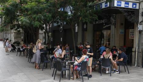 Imatge d'una terrassa d'un bar amb clients al costat de la plaça Sant Joan de Lleida ciutat.