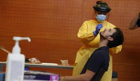 Imatge d'un sanitari fent la PCR a un jove al centre cívic de Balàfia.