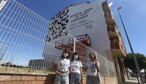 L'artista Cristina Dejuan, al mig, ahir davant del mural censurat a Torrefarrera.