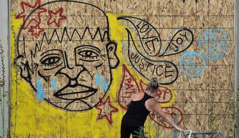 Una manifestant va ser registrada per pintar un mural.