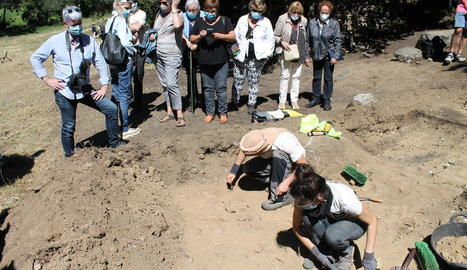 Familiars dels afusellats observen com els arqueòlegs van trobant restes a la fossa.