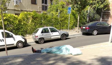 Imatge d'un home dormint a ple sol al barri.