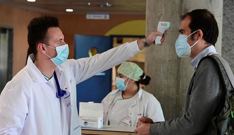 Control de temperatura per entrar en un hospital a Madrid, comunitat que suma més contagis.