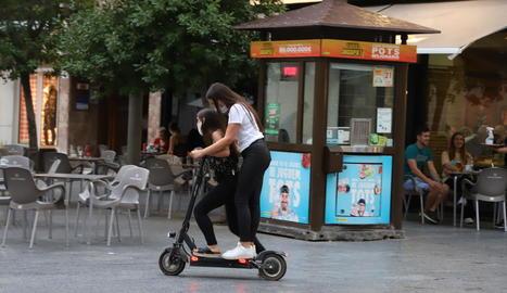 Dos joves circulant en patinet elèctric per l'Eix, ahir.