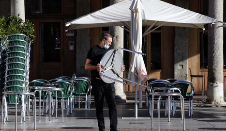 Un cambrer munta la taula d'una terrassa a Valladolid.