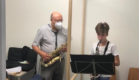 Un professor de l'Escola Municipal de Música de Balaguer, fent classes de saxo rere una mampara.