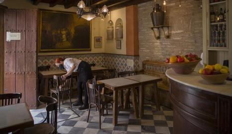 Una cambrera desinfecta les cadires en un bar de Sevilla.