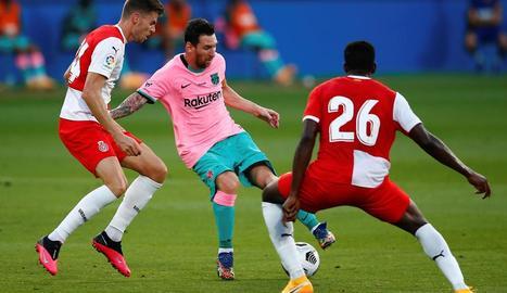 Leo Messi controla la pilota davant de Gumbau i Ibrahim Kebe, jugadors del Girona.