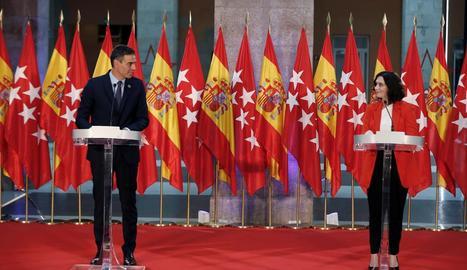 Sánchez i Ayuso van escenificar l'aposta de col·laboració davant de 24 banderes d'Espanya i Madrid.