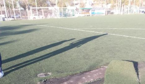 Un membre de la UE Balàfia al reparar ahir un tros de gespa. A la dreta, detall d'una altra zona aixecada del terreny de joc.