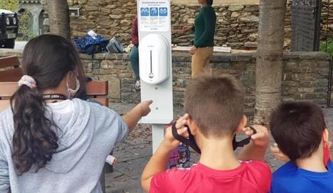 Nens amb un dels dispensadors de gel de Rialp.
