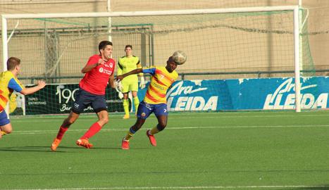 Pau Solanes, del Balaguer, pugna amb un jugador rival pel control de la pilota.