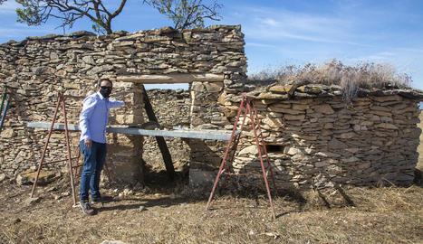 L'alcalde, Jaume Pané, vora una de les cabanes que restauren.