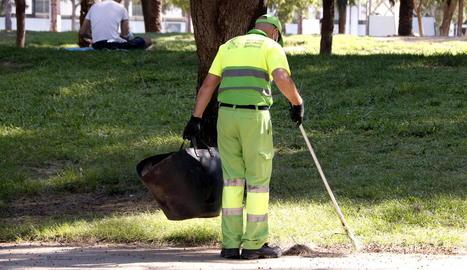 Imatge d'un membre del servei de neteja escombrant el parc de la Barceloneta.