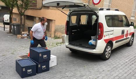 Un voluntari de Creu Roja Lleida repartint aliments per als usuaris del menjador social Jericó, aquest estiu.