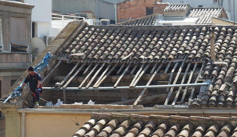 Un operari treballant ahir a la zona de la teulada de la capella que es va enfonsar al juliol per les pluges.