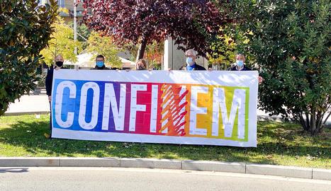Membres de l'associació amb la pancarta que anima els seus socis a no llançar la tovallola.