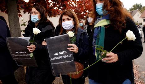 Diverses companyes del professor assassinat porten flors per honrar la víctima.