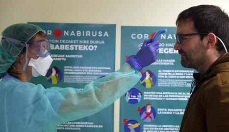 Una infermera pren la temperatura un pacient a l'entrada d'un centre de salut a Euskadi.