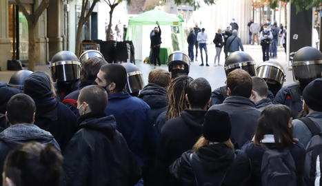 En primer pla, els manifestants i els antiavalots. Al fons, l'estand de Vox al carrer Major.