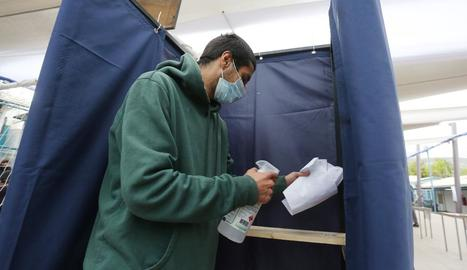Un home desinfecta una cabina de votació en un col·legi electoral a Santiago de Xile.