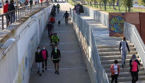Un dels accessos a la canalització del riu Segre a Lleida, amb ciclistes i passejants, ahir.